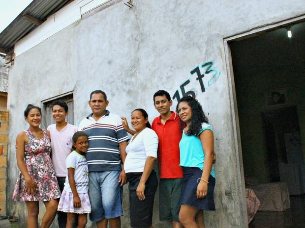 Família de Valmir na frente da casa construída com dinheiro adquirido enquanto trabalhava no hotel (Foto: Leandro Tapajós/G1 AM)